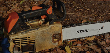 A Stihl chainsaw on the ground after tree trimming