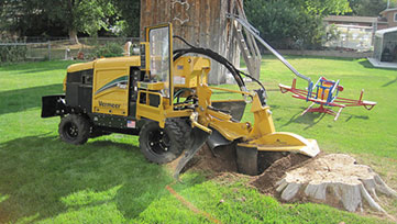 A stump grinding machine removing a stump in a garden